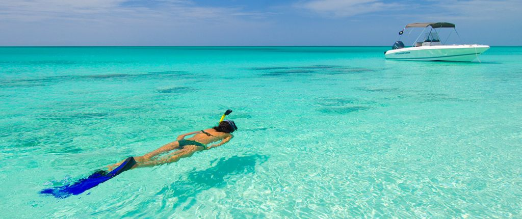 Diver in pristine turquoise water of grace bay beach near to the villa rental